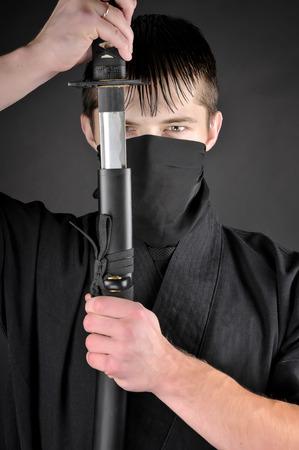 combative sport: Ninja - spy, saboteur, stealth assassin of feudal Japan. Close-up portrait of Ninja with sword.
