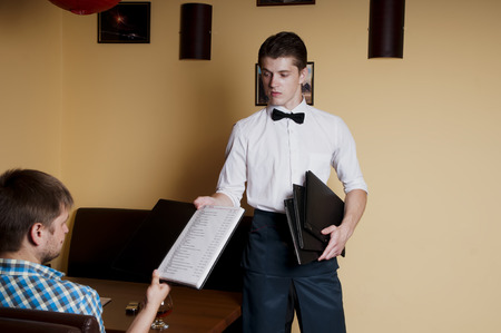 Man makes an order  to the waiter at a restaurant. photo