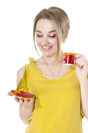 cosily: Smiling woman with cup of coffee on a plate, isolated on white background.
