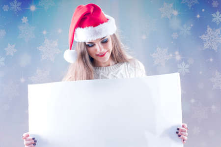 Happy young christmas girl holding a blank paper sign, isolated on snowy background. photo