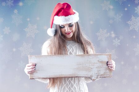 Christmas girl holding an empty wooden  board for text, isolated on snowy background. photo