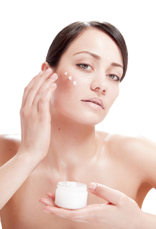 humidify: Beautiful woman applying cosmetic cream treatment on her face. Skin care concept. Stock Photo