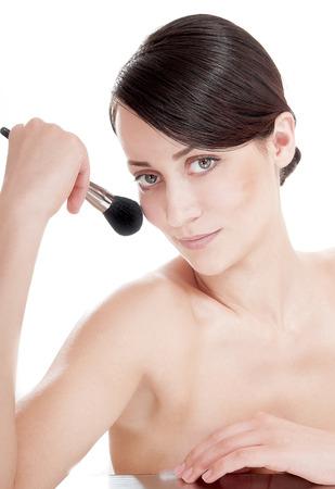 primp: Giovane bella ragazza che applica polvere a pennello sul suo viso.