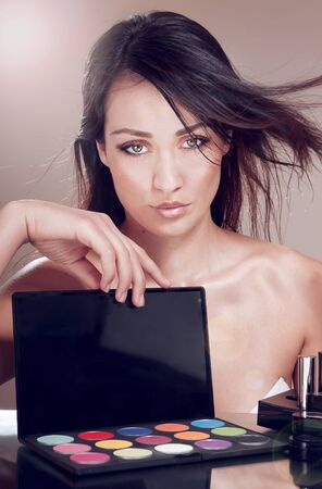 Seductive woman with cosmetics for makeup. photo