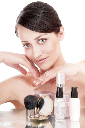 complexion: Woman with a good complexion near the creams cosmetics. Skin care concept.