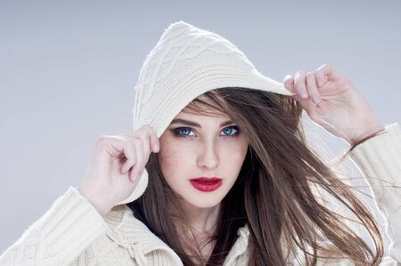 makeups: Beautiful charming woman in hood,  over blue background.
