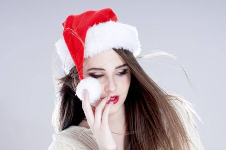 Christmas woman. Beautiful charming girl wearing  santa hat over blue background. photo