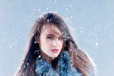 makeups: Winter fashion woman in a fur coat over snowy background. Stock Photo