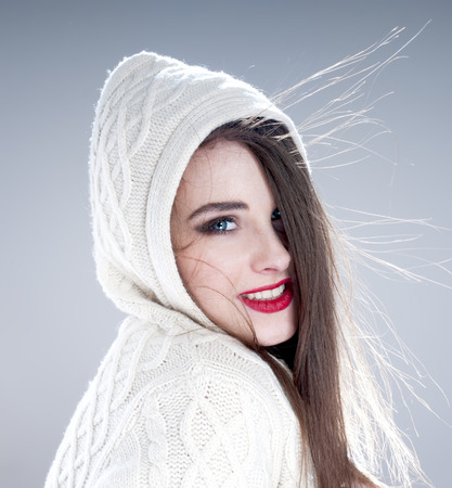 makeups: Beautiful charming woman in knitted  hood,  over blue background. Stock Photo