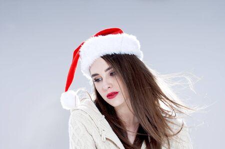 Christmas woman. Beautiful charming girl wearing  santa hat over blue background. photo