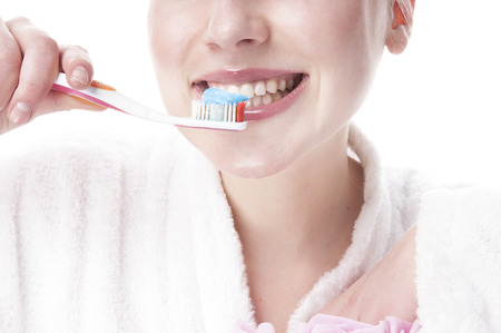 Woman  brushing her teeth - isolated on white background. photo
