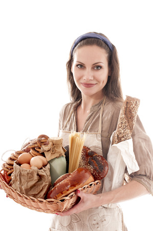 Young housewife holding a wicker tray with different food. photo