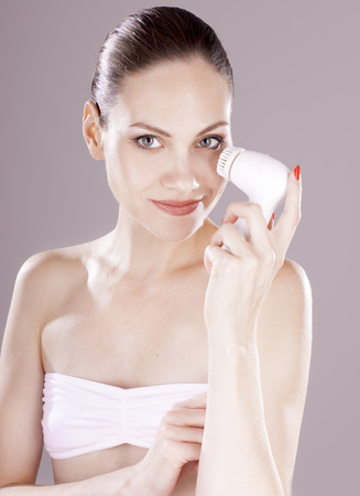 humidify: Charming woman with brush for deep cleansing facial. Skin care concept. High technology beauty.