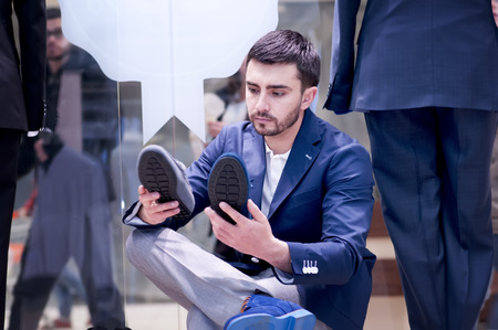 Attractive young  man chooses a shoes  at a shop. photo