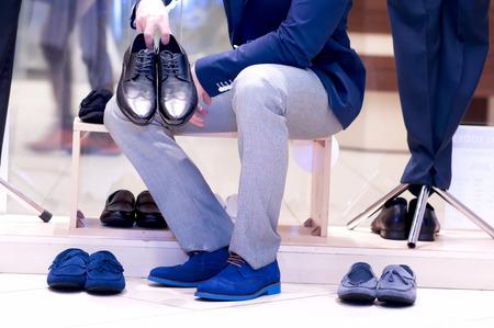 buying shoes: Hombre joven atractivo que elige los zapatos en una tienda. Foto de archivo