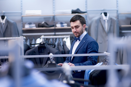 Handsome man in boutique of clothing.