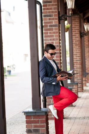 moccasins: Stylish handsome man reading a magazine on walks.