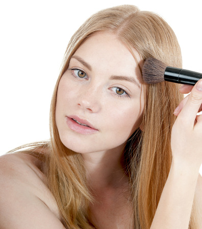 primp: Young beautiful girl applying powder by brush on her face.