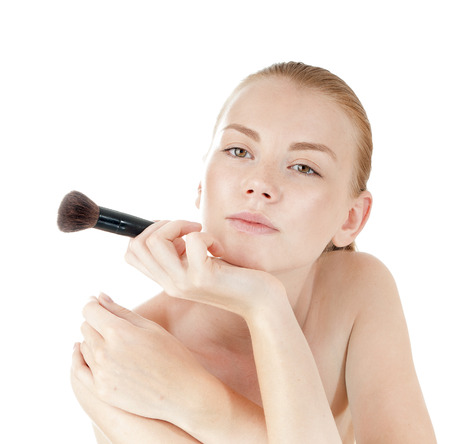 primp: Young beautiful girl applying makeup by brush on her face. Stock Photo