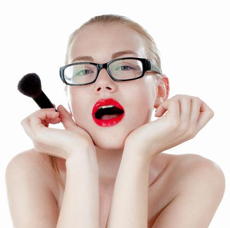 primp: Astuta bella ragazza con un spazzole per trucco con gli occhiali neri.