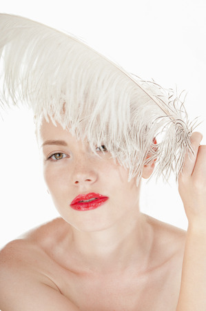 whithe: Beautiful young girl with a white feather. Spy beauty skin treatment woman. Healthy lifestyle concept. Stock Photo