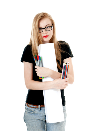 denim shorts: Happy young girl with  colored pencils, felt-tip  and white roll paper, wearing black t-shirt, denim shorts, glasses.  Creativity concept. Stock Photo