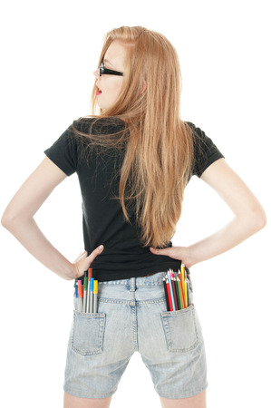 denim shorts: Young girl with lots of colored pencils and felt- tip in her pockets of denim shorts.  Creativity concept. View from the back.