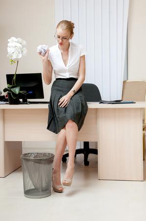 wastepaper basket: Yong businesswoman gettando carta sgualciti in un cestino della carta straccia.