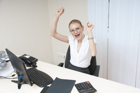 Business woman celebrating victory at the laptop computer. photo