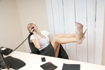 laughing business woman on landline phone call, listening to conversation. photo