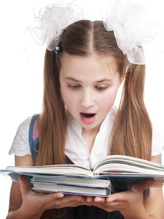 textbook: Surprised schoolgirl reading textbook on white background. Stock Photo