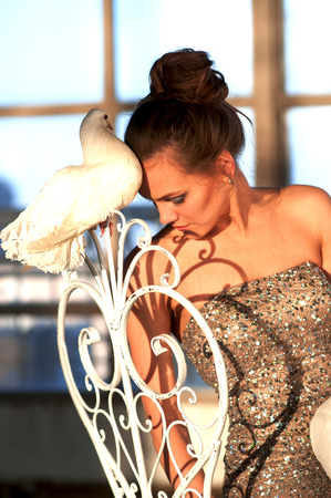 Graceful girl with a white dove sitting on a chair.