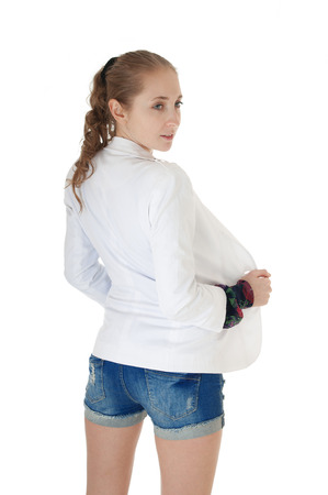 Rear view of woman dressed in  blue jeans shorts and  white jacket, isolated  on white background. photo