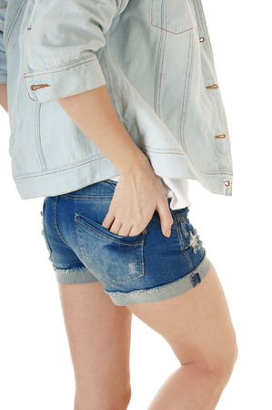 Side view of female body and legs in  blue jeans shorts and  denim jacket, isolated  on white background. photo