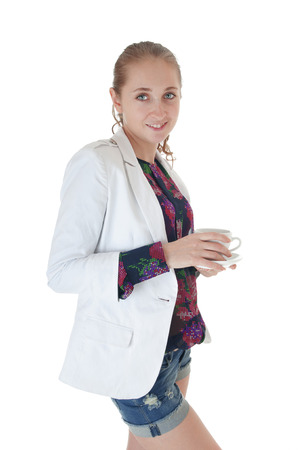 cosily: Young beautiful smiling girl holding cup with saucer in white jacket and jeans shorts against white background.