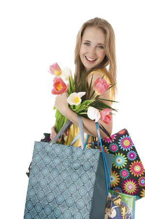 Portrait of a happy smiling  girl with a bouquet of spring tulips in hands and shopping gift bags on a white background Womens day concept photo