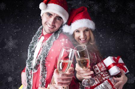 snowy background: Pares divertidos de Navidad con copas de champ�n que cubren fondo cubierto de nieve