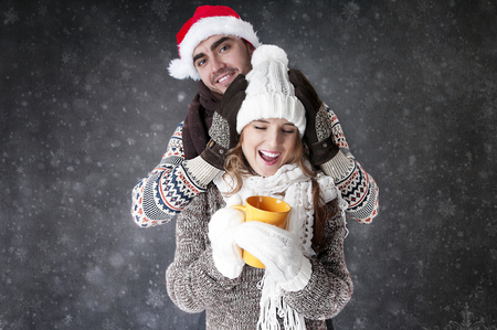 to get warm: Happy funny couple  with a cup of tea covering  snow background.   Have a warm. Fool around.