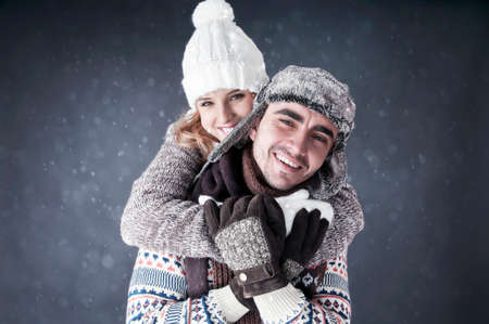 Happy young couple   covering  snow background photo