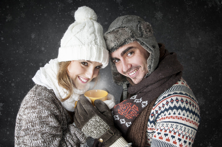 dearly: Happy young couple  with a cup of tea covering  snow background.   Have a warm.