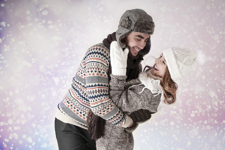 to get warm: Happy funny couple covering  snow background.   Have a warm. Fool around.