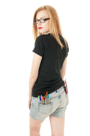 denim shorts: Young girl with lots of colored pencils and felt- tip in her pockets of denim shorts. Creativity concept. View from the back. Stock Photo