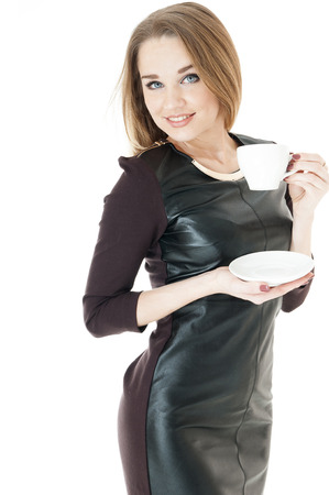 cosily: Elegant  woman in a  leather short dress   holding cup and saucer against white background.