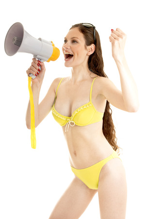 Summer  girl wearing a yellow swimsuit and  holds a megaphone near the mouth.Isolated on white background. photo