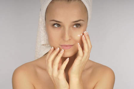humidify: Beautiful woman in a white towel applying moisturizer cream on face.