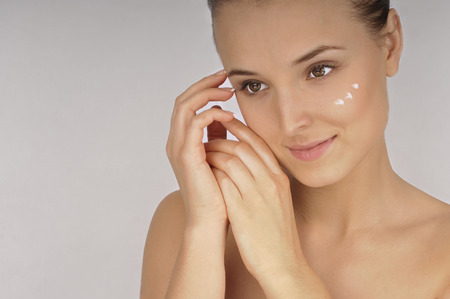 humidify: Beautiful woman applying moisturizer cream on face.