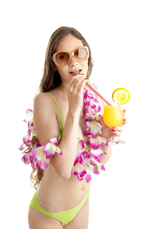 lei: Portrait of beautiful woman in bikini wearing flower lei garland of pink orchids and holds orange cocktail over white background.