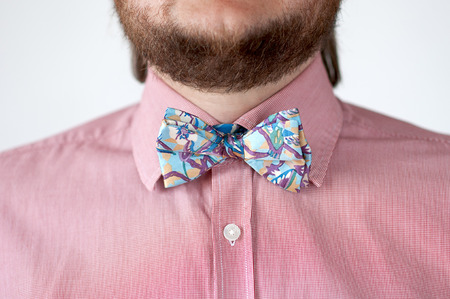 pedantic: Colorful bow tie with pink shirt  on mens neck.