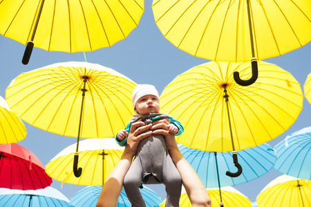 Newborn baby in her arms raised under a colorful umbrellas.