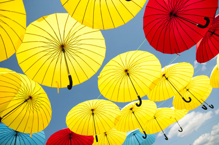 Yellow and blue, red umbrellas under a cloudy sky. photo